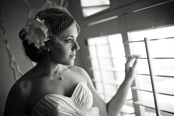 Black and white of bride looking out the window- wearing a cage veil with flower accent  and strapless dress -