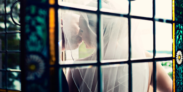 Beautiful photo by 2 Brides Photography of couple kissing behind window.