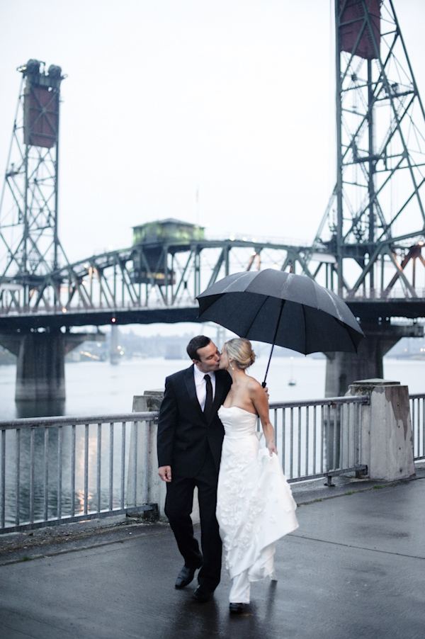 the newlywed kissing in the rain on waterfront -  wedding photo by top Portland, Oregon wedding photographer Aaron Courter