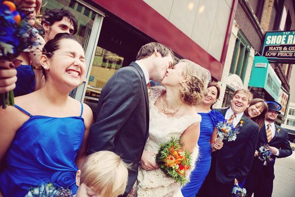 Adorable wedding photo by Abby Rose Photography of couple kissing surrounded by wedding party.