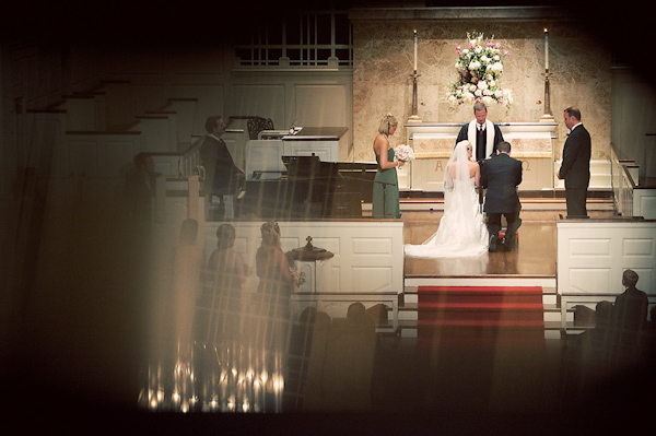 Beautiful photo of bride and groom kneeling to pray at the altar of the church during the ceremony photo -  by Houston based wedding photographer Adam Nyholt