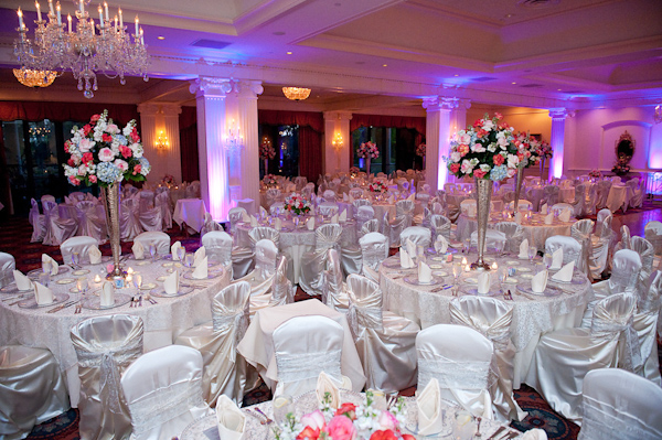 Beautiful Indoor Reception Seating Area Crystal Chandeliers Purple Light Effects Tables And Chairs Decorated In White Silk Centerpieces Of Silver