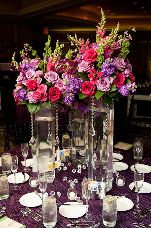 table setting at reception - three tall glass vases with danging crystals with dark pink, light pink, purple, and green floral arrangements as centerpiece and purple tablecloth - photo by Houston based wedding photographer Adam Nyholt