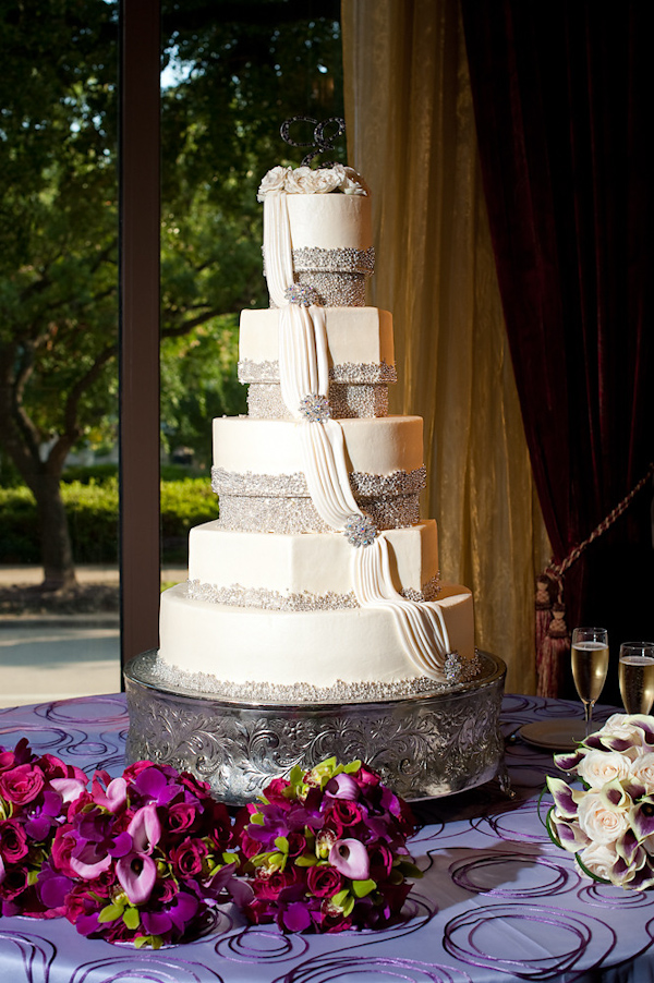 White Five Tiered Wedding Cake With Silver Beaded Borders And A Ivory Drape Brooches On Each Layer Is Vintage Style Stand