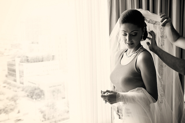 sepia photo - beautiful bride having her full length veil put as she stands next to a large window overlooking the city - photo by Houston based wedding photographer Adam Nyholt