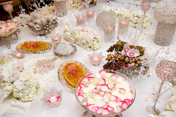 beautiful reception tabletop decor - crystal candle holders,vases, and punchbowls with pink, white, ivory, and green floral accessories - photo by Houston based wedding photographer Adam Nyholt