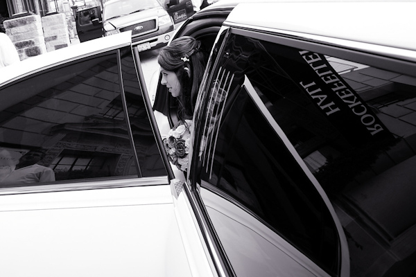 black and white photo of the bride arriving at the ceremony location, Rockefeller Hall, in a limousine with the location's sign reflected in the window - photo by Houston based wedding photographer Adam Nyholt