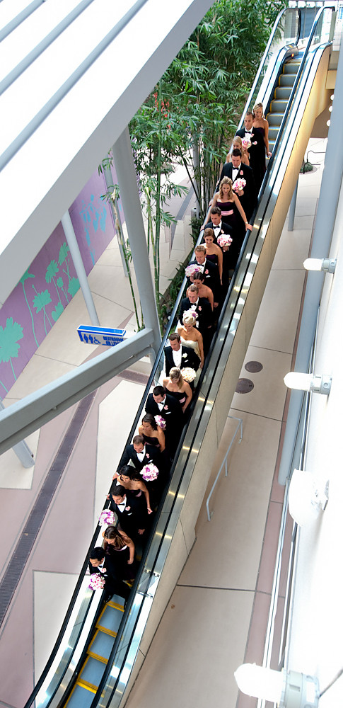 the bride and groom  going down escalator with groomsmen and bridesmaids - photo by Houston based wedding photographer Adam Nyholt