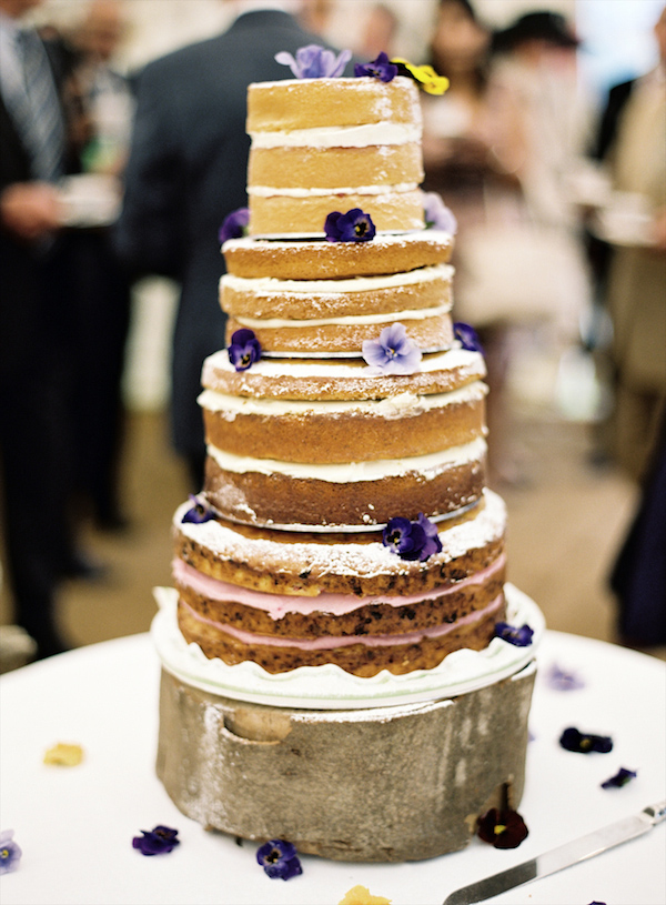 Rustic, homemade tiered wedding cake with purple flower details - Photo by Aneta MAK