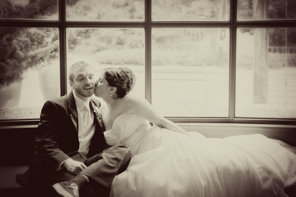 Sepia photo - Bride kissing groom while lounging on window seat - photo by Portland wedding photographer Barbie Hull