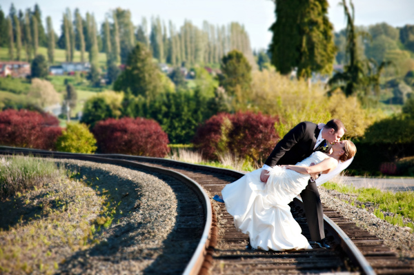 Groom dipping bride for a kiss while standing on railroad track in the beautiful countryside - photo by Portland wedding photographer Barbie Hull