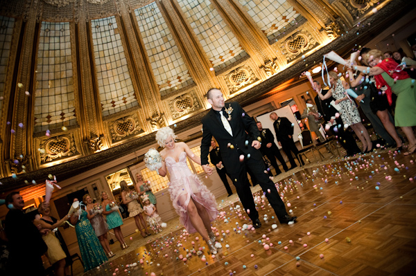 Beautiful photo of bride and groom exiting the ceremony held in a gorgeous historic site while guests throw small multi colored balls at them - Bride is wearing short pink dress with ruffles and groom is wearing a black suit with a light pink tie - photo by Portland wedding photographer Barbie Hull
