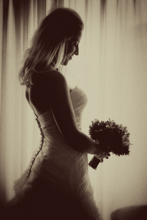 Sepia photo - Profile of beautiful bride looking down at her bouquet - photo by Portland wedding photographer Barbie Hull