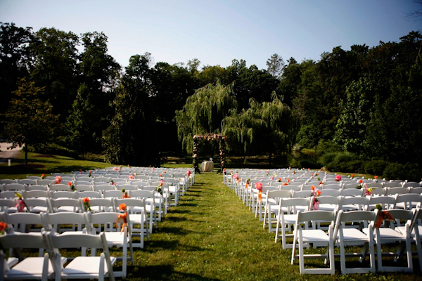 outdoor ceremony with white chairs and floral accents - grass aisle -  charming Hudson Valley NY wedding photo by top New York wedding photographers Belathee Photography