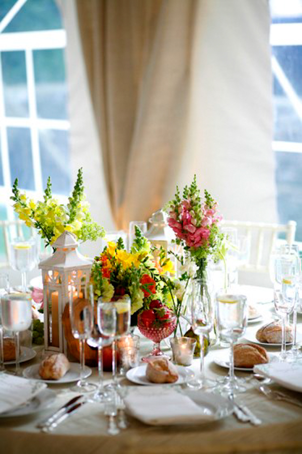 floral centerpiece and table setting in a tented reception site - charming Hudson Valley NY wedding photo by top New York wedding photographers Belathee Photography