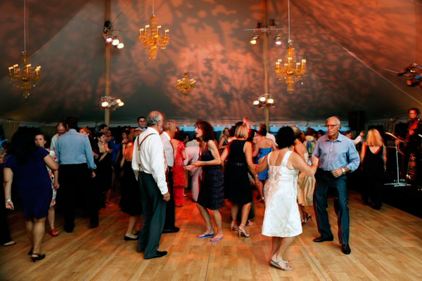 dancing in tented reception site - gold chandeliers and wooden floor - charming Hudson Valley NY wedding photo by top New York wedding photographers Belathee Photography