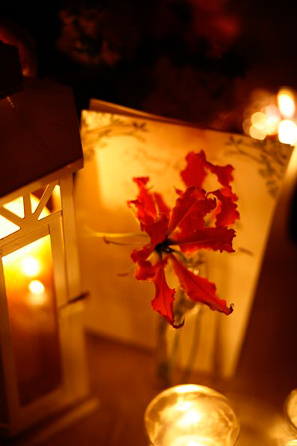 red flower by candles and lantern - charming Hudson Valley NY wedding photo by top New York wedding photographers Belathee Photography