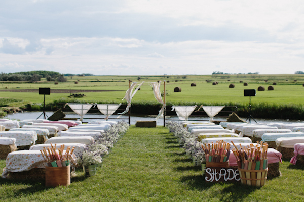 Outdoor ceremony seating with luscious green fields - wedding photo by Michigan-based wedding photographers Bryan and Mae