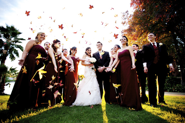 group portrait of the newlywed and guests tossing leaves into the air - wedding photo by top Orange County, California wedding photographers D. Park Photography