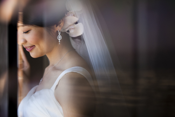 smiling bride looking out window - wedding photo by top Orange County, California wedding photographers D. Park Photography