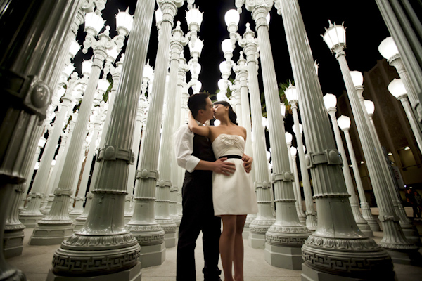 the happy couple kissing surrounded by light posts - wedding photo by top Orange County, California wedding photographers D. Park Photography