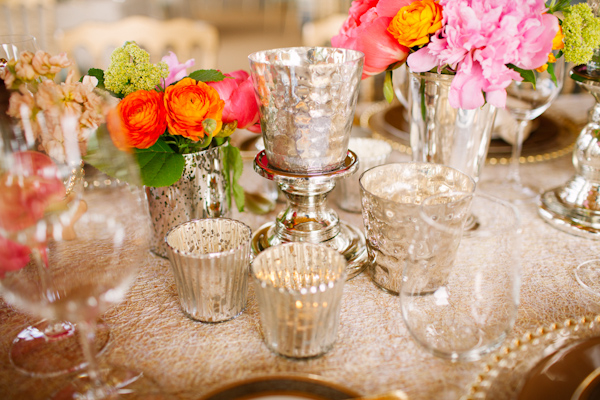 Vintage inspired silver table decor flanked by bright pink and coral flowers - photo by Dan Stewart Photography
