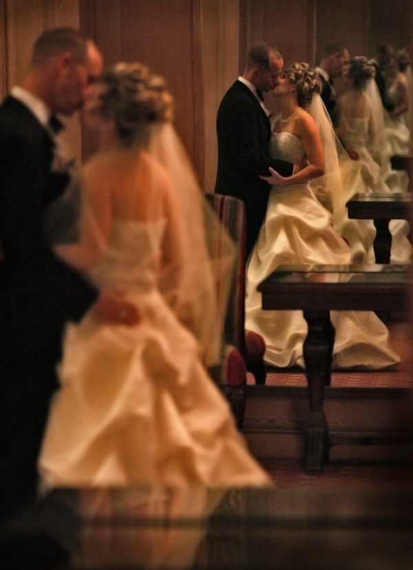 Bride, in ruffled ball gown and elbow length veil, and groom kiss in a hall of mirrors wedding photo by David Beckstead