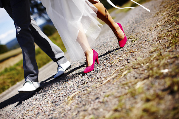 the happy couple walking down road -  red shoes of bride - wedding photo by top Swedish wedding photographers Dayfotografi