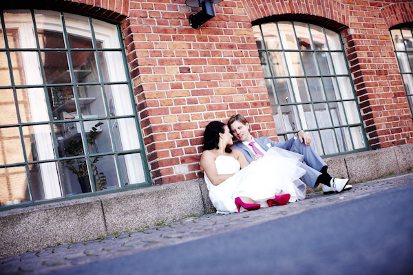the happy couple sitting against wall in urban setting - wedding photo by top Swedish wedding photographers Dayfotografi