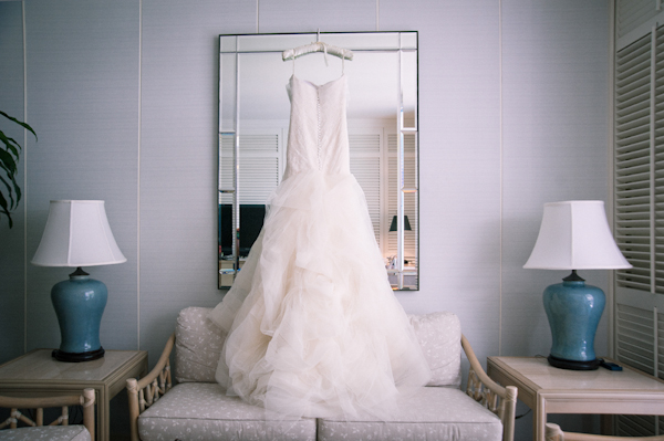 ball gown wedding dress hangs in front of mirror - Honolulu destination wedding photo by top Hawaiian wedding photographer Derek Wong