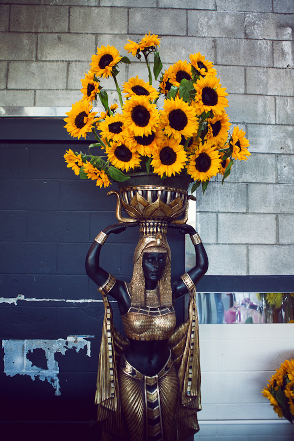 Egyptian statue decor with sunflower bouquet - vintage LA wedding at The Smog Shoppe photo by top Orange County wedding photographer Duke Images