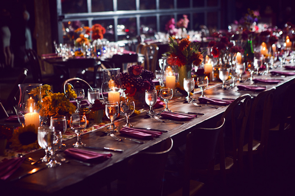 flowers and assorted candles line a long table in a warehouse reception site - vintage LA wedding at The Smog Shoppe photo by top Orange County wedding photographer Duke Images