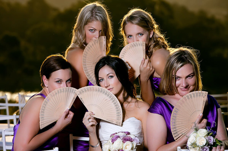 Bride in white dress and bridesmaids in purple dresses