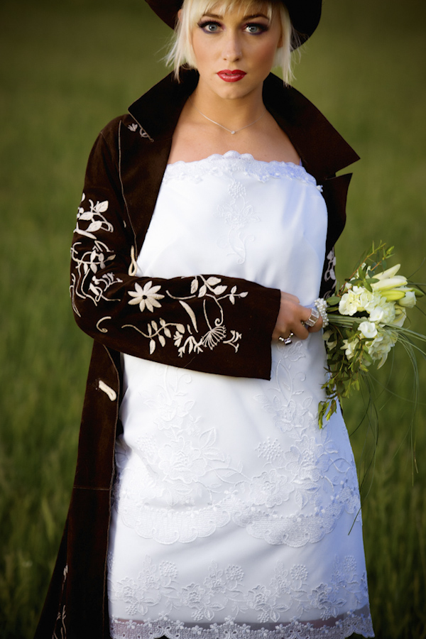bride wearing cloak with flowery design and holding bouquet - wedding photo by top Denver based wedding photographer Hardy Klahold
