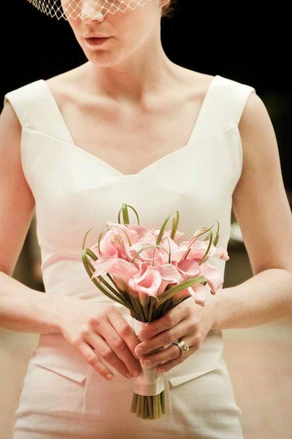 bride wearing a form fitted ivory dress holding a beautiful bouquet of pink calla lilies - photo by Washington DC based wedding photographers Holland Photo Arts