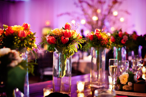 centerpieces on reception seating tables of dark pink tulips with dark green and light green fillers - photo by Washington DC wedding photographers Holland Photo Arts