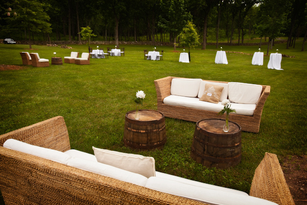 outdoor reception lounge seating area with wicker loveseats with white cushions, tables made from barrels with white rose decor - photo by Washington DC based wedding photographers Holland Photo Arts