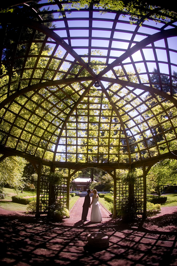 Bride and groom kissing in garden gazebo - wedding photo by J Garner Photographer