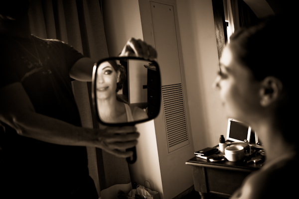 Sepia photo - Beautiful bride looking into hand mirror after she has had her makeup applied - photo by North Carolina based wedding photographer Jeremie Barlow