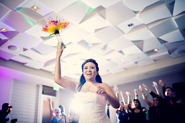 Bride tossing a yellow, orange, and purple bouquet - photo by Florida based wedding photographer Kat Braman