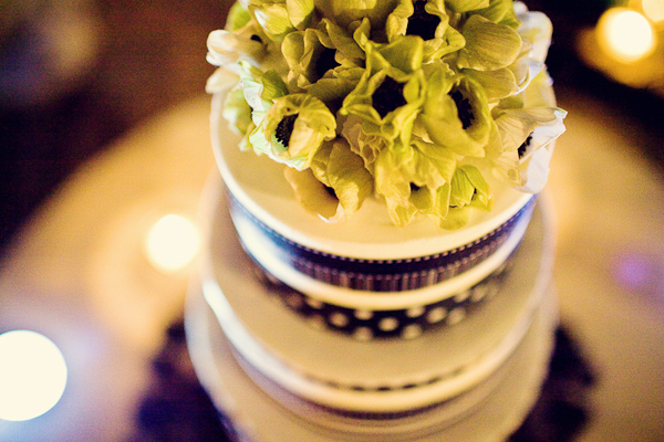 White tiered wedding cake with purple borders and light green floral details - photo by Florida based wedding photographer Kat Braman