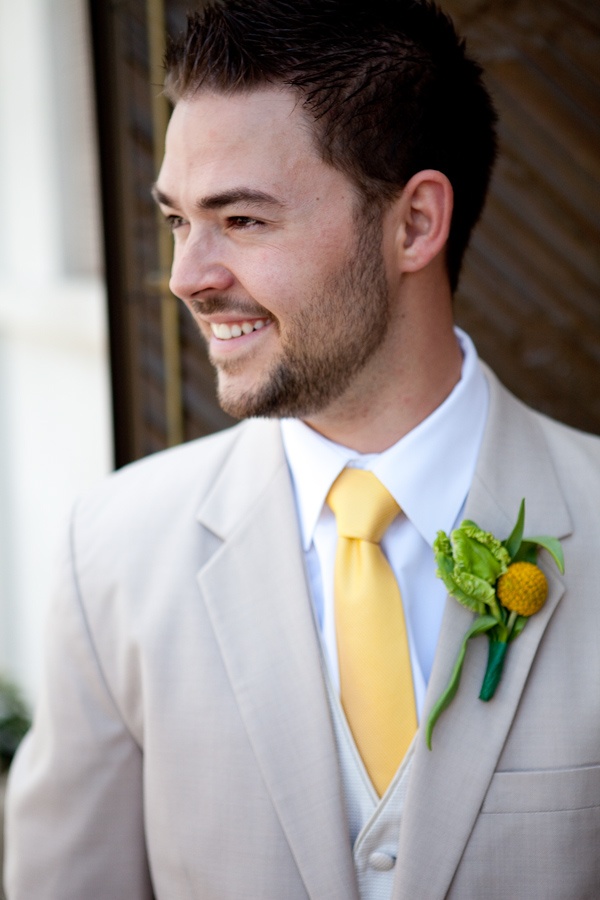 smiling groom in light gray suit with golden yellow tie and ...