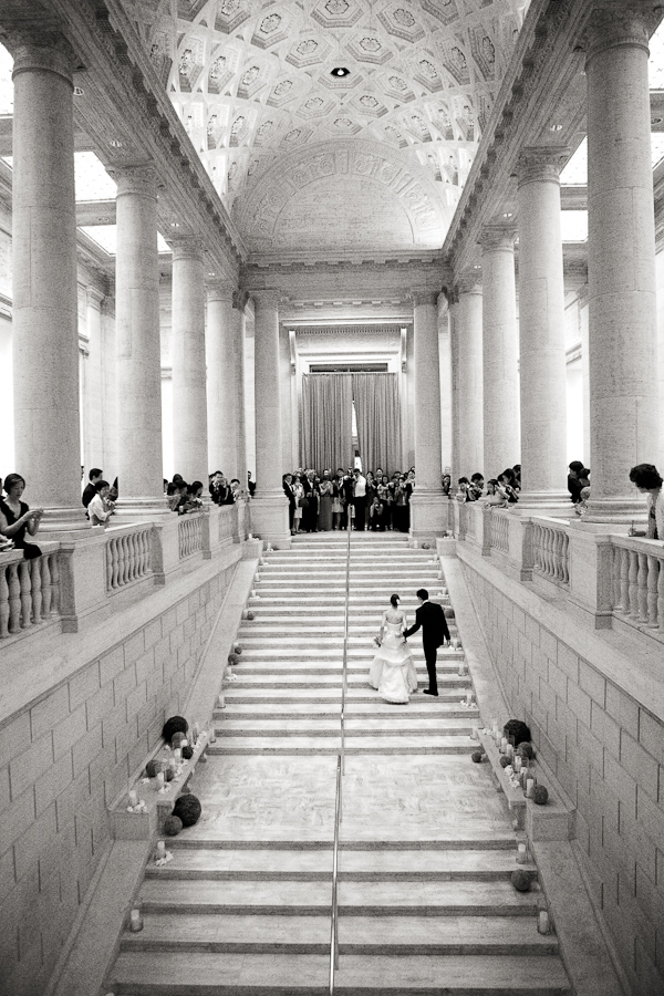 black and white photo of the happy couple walking up grand staircase - photo by San Francisco based wedding photographer Lisa Lefkowitz