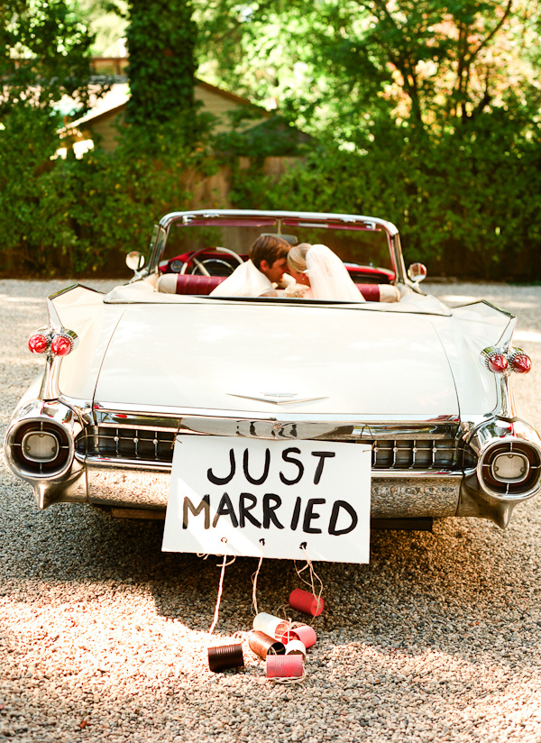 the happy couple in vintage car leaving reception with just married ...
