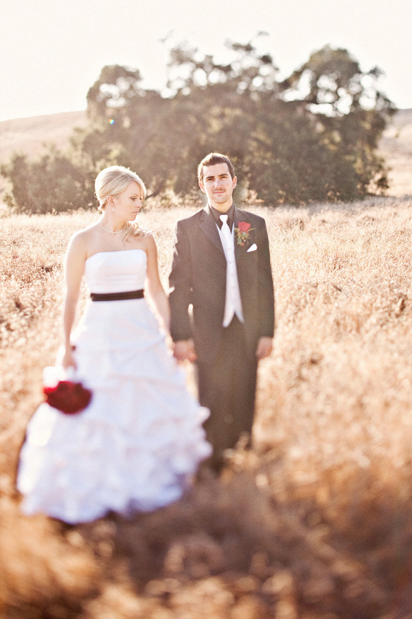 Bride And Groom Standing In An Open Field Bride Is Wearing White