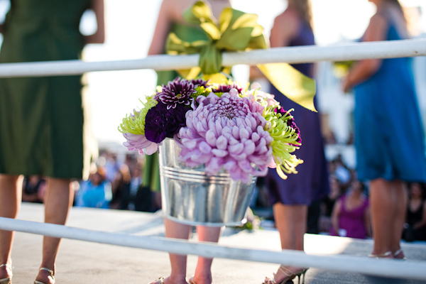Ceremony floral detail - purple, lavender, and light green floral arrangement in a tin bucket hanging by a light green ribbon - photo by Orange County based wedding photographers Mark Brooke