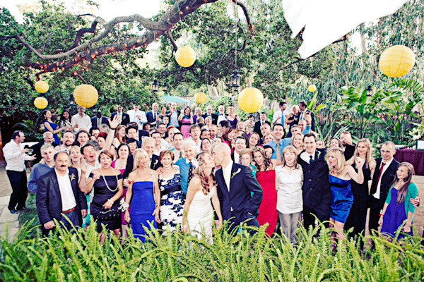 group portrait - the happy couple kissing in front of friends and family - photo by Southern California wedding photographer Meg Perotti