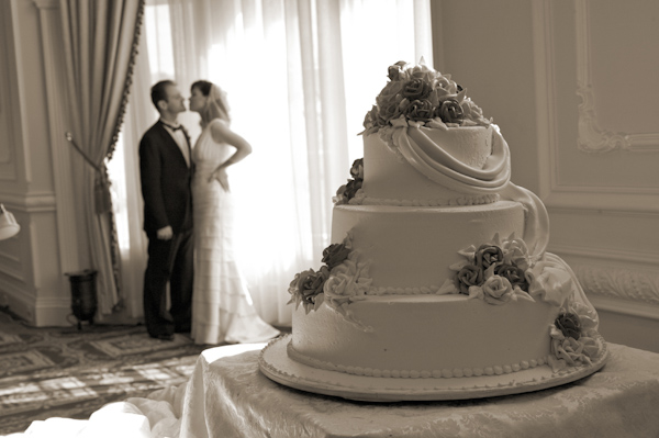 photo by New York based wedding photographer Merri Cry - sepia photo of a three tier wedding cake - bride and groom kissing our of focus in the back ground
