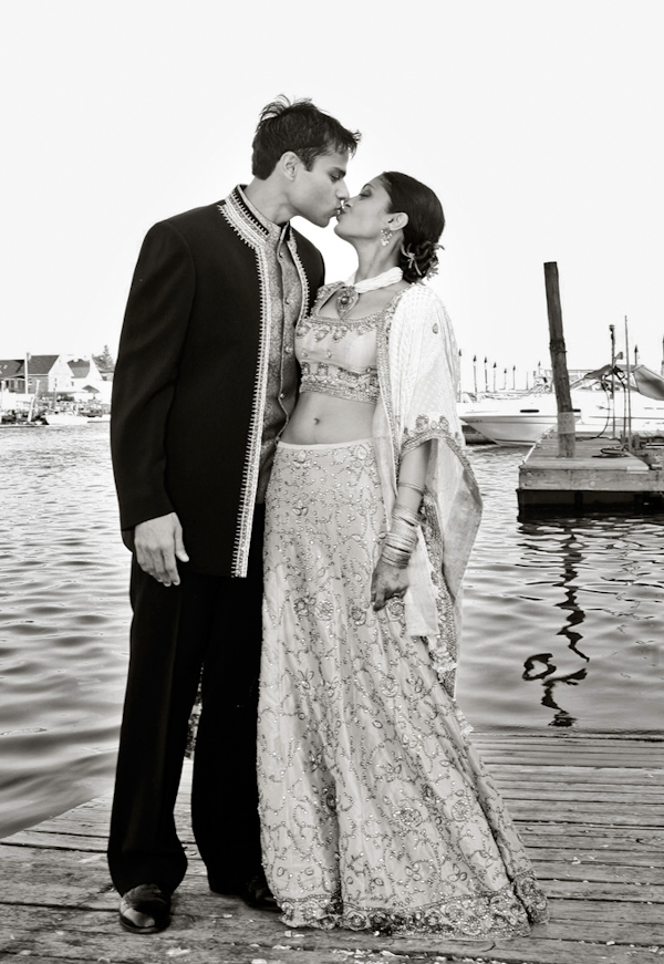 photo by New York based wedding photographer Merri Cry - the happy couple kissing on a dock - indian wedding