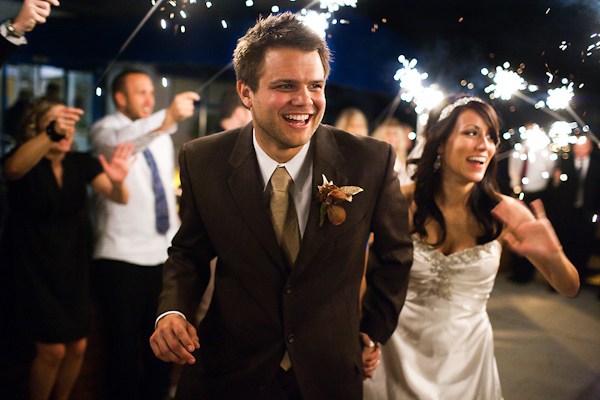 Bride And Groom Leaving The Wedding Reception With Guests Holding Sparklers Is Wearing Brown